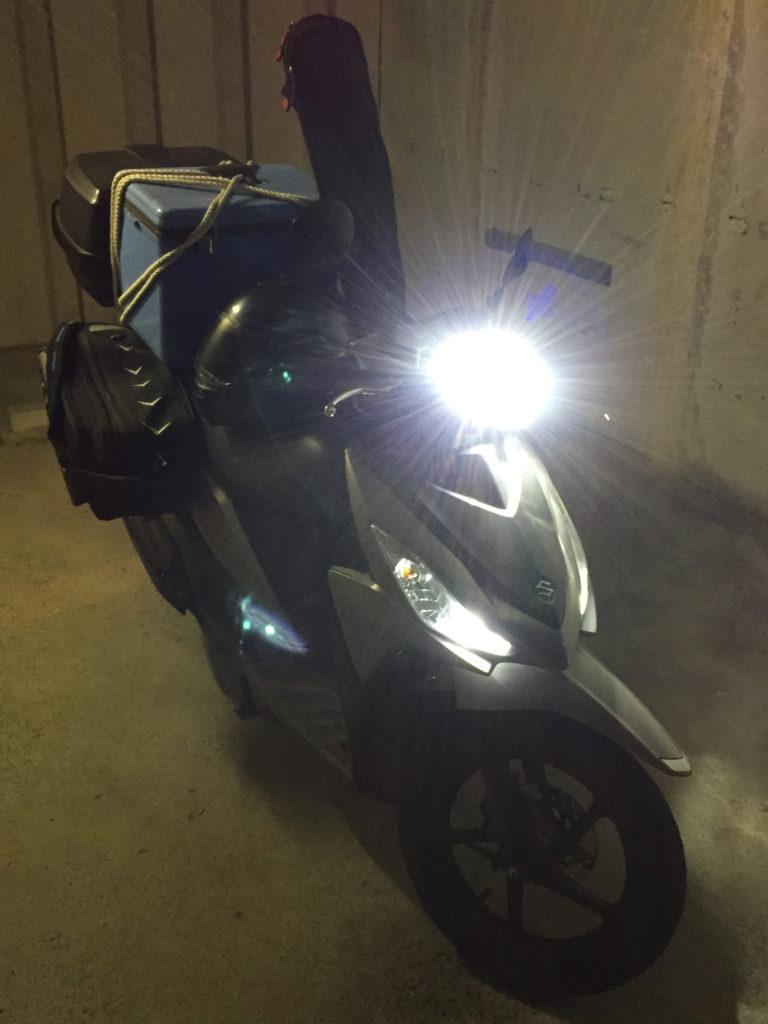 バイクで完全装備。リアボックスにバッテリーと魚探、サイドバッグに仕掛けとリール、クーラーはタンデムシートにロープで縛って、ロッドは背にかけて運転。